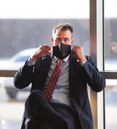 Gov. Kevin Stitt is seen putting on a mask after speaking to reporters at Integris Baptist Medical Center in Oklahoma City on Dec. 14, 2020. Whitney Bryen/Oklahoma Watch Watonga Republican